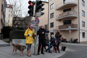 """Passanten warten auf der """"Roten Bank"""" am Gasteig-Kircherl (©MarcelSenf)"""