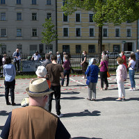 Zuhörer bei der Einführung durch Hermann Wilhelm (im Hintergrund am Zaun)