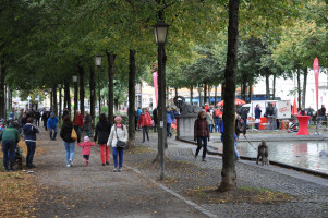 Totale vom Bordeauxplatz, Brunnen, SPD-Schirme, Personen im Gespräch und beim Spielen